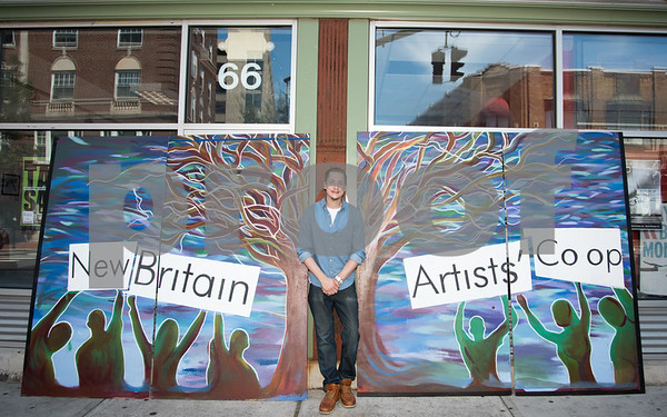 081717 Wesley Bunnell | Staff New Britain Co-op artist Kendall Soliwoda of KRS Studios poses with a new community mural which was primarily designed and painted by him. The mural is to be eventually installed on an upper floor of the building at 66 West Main St.