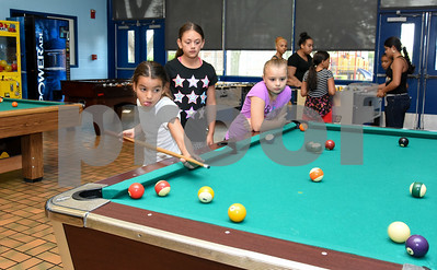 081117  Wesley Bunnell | Staff  Yamaris Nevarez, age 8, sticks her tongue out as she shoots in a game of pool alongside Aymara Soler, age 10, and Brooke Barriault, age 8, at The Boys & Girls Club of New Britain on Friday afternoon.