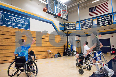 080217  Wesley Bunnell | Staff  Volunteers David, L, and Kyle McCormick, middle, play basketball with camper Joe Grindrod during the Hospital for Special Care Ivan Lendl Adaptive Sports Camp on Wednesday afternoon at the University of St. Joseph in West Hartford.