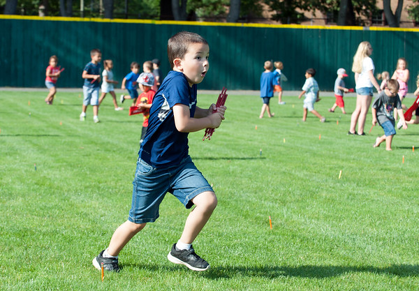 08/21/18 Wesley Bunnell | Staff Christopher Halpin, age 6, runs with his red pencils during the 1st Annual Mayor's Back to School Pencil Hunt at Muzzy Field on Tuesday afternoon. The event featured 500 children in age specific groups in grades K-8th searching for specific colored pencils on the field to win prizes.