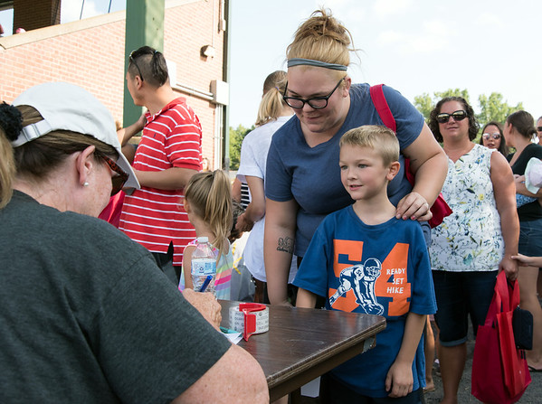 08/21/18 Wesley Bunnell | Staff Dylan Ruffles, age 6, stands with his mother in line to check in for the 1st Annual Mayor's Back to School Pencil Hunt at Muzzy Field on Tuesday afternoon. The event featured 500 children in age specific groups in grades K-8th searching for specific colored pencils on the field to win prizes.
