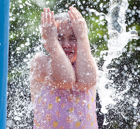 08/21/18 Wesley Bunnell | Staff Jelani Ruiz, age 11, stands under a stream of water at the Willow Street Splash Pad on Tuesday afternoon.