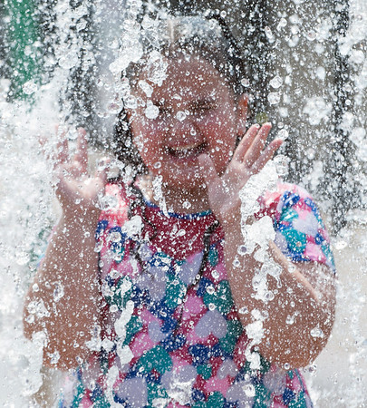 08/21/18 Wesley Bunnell | Staff Jaridel Burgos, age 8, stands under a heavy stream of water at the Willow Street Splash Pad on Tuesday afternoon.