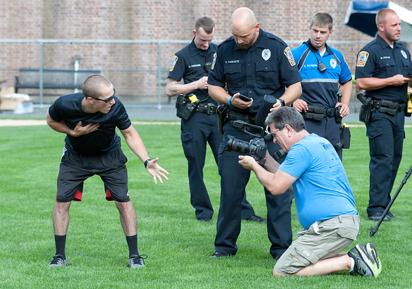 08/21/18 Wesley Bunnell | Staff Bristol first responders filmed portions of their lip sync challenge video at Muzzy Field on Tuesday afternoon before the Mayor's Pencil Hunt. Ofc. Mike Marino, L, sings as Tom Mazzarella of Mazzarella Productions records.