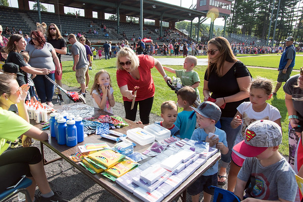 08/21/18 Wesley Bunnell | Staff Cassidy Cook, middle, helps her daughter Chloe, age 5, pick out a prize after the 1st Annual Mayor's Back to School Pencil Hunt at Muzzy Field on Tuesday afternoon. The event featured 500 children in age specific groups in grades K-8th searching for specific colored pencils on the field to win prizes.