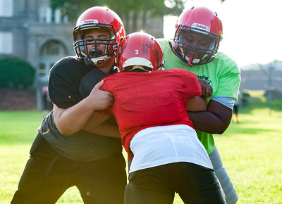 08/22/18  Wesley Bunnell | Staff  Jaiden Fore, middle, takes on Christian Lamanaco, L, and J'Kai Hickey-Davis, R, during double team blocking drills for the 7th grade Bristol Bulldogs on Wednesday evening at Memorial Boulevard Field.