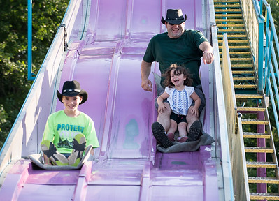 08/24/18  Wesley Bunnell | Staff  Shawn Alexander Jr ,age 13, rides down the slide next to his father Shawn Alexander and his niece Emilie Torneo, age 4 at the Terryville Fair on Friday afternoon.