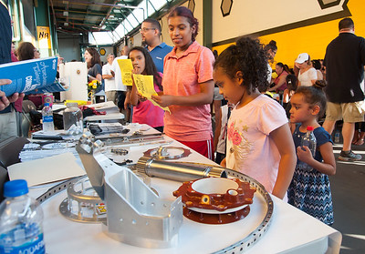 08/28/18  Wesley Bunnell | Staff  Amanda Valdes, middle, looks on as daughters Maiya Valdes, age 6, and Adeline Valdes, age 5, look over the NBHS 's Academy of Engineering, Manufacturing and IT table which features components from Richards Machine Tool in Newington during the CSDNB annual Back to School Bash on Tuesday evening. Richards Machine Tool Owner Dorothy Weber is a member of the academy's advisory board. Currently two NBHS graduates work at Richards as well as a current senior intern. The bash was held at New Britain Stadium prior to the New Britain Bees game vs the York Revolution and helps to introduce students to school staff prior to the school year as well as provide free admission to the Bees baseball game.