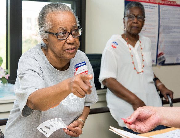 08/14/18 Wesley Bunnell | Staff Ballet Clerk Margaret Shorter explains the voting procedure to a voter at voting district 5-1 at the School Apartments on Bassett St on Tuesday afternoon.