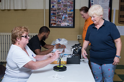 08/14/18  Wesley Bunnell | Staff  Pam Elabianca checks in with Official Checker Izabella Szczepanski , L, while Jerome Hardy, rear, checks in Lynn Reid at the St. Francis of Assisi Church Hall voting location on Tuesday afternoon.