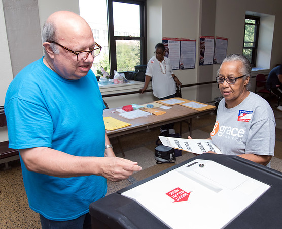 08/14/18 Wesley Bunnell | Staff William Eltman enters his voting ballot into the tabulation machine under the watch of Ballot Clerk Margaret Shorter at voting district 5-1 at the School Apartments on Bassett St on Tuesday afternoon.