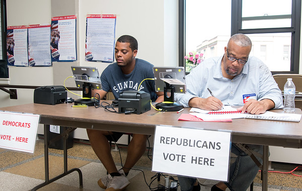 08/14/18 Wesley Bunnell | Staff Assistant Registrar Christian Hardy, L, fills in for an official checker as he sits next to his father, Official Checker Harry Hardy, at voting district 5-1 at the School Apartments on Bassett St on Tuesday afternoon.
