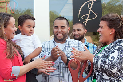 08/29/18  Wesley Bunnell | Staff  Minerva Cardona holds son Jace Ruiz, age 2, as she stands next to her husband Jesus Ruiz at the opening of J's Auto Sales and Repair LLC located at 866 West Main St in New Britain just before the official ribbon cutting as Mayor Erin Stewart looks on.