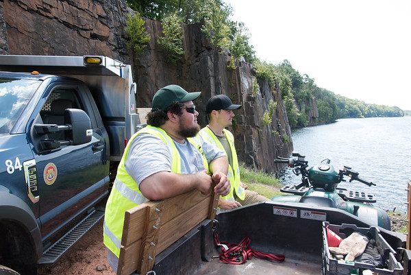 08/29/18 Wesley Bunnell | Staff Utility workers Derick Brown, L, and Justin Thompson keep an eye out for trespassers cliff diving at Shuttle Meadow Reservoir on Wednesday afternoon.