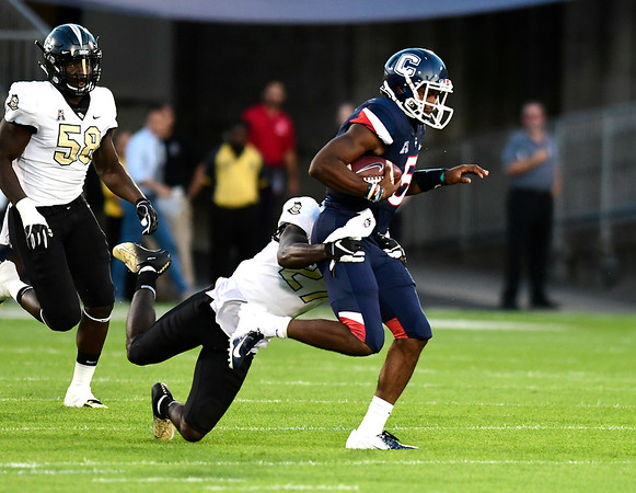 8/30/2018 Mike Orazzi | Staff UConn quarterback David Pindell (5) andUCF's Richie Grant (27) at Rentschler Field in East Hartford Thursday night.