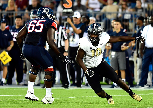 8/30/2018 Mike Orazzi | Staff UConn's Matt Peart (65) and UCF's Titus Davis (10) at Rentschler Field in East Hartford Thursday night.