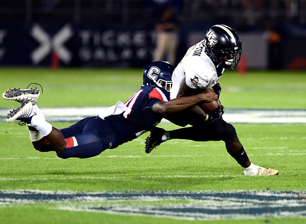8/30/2018 Mike Orazzi | Staff UConn's Keyshawn Paul (24) and UCF's Tristan Payton (6) at Rentschler Field in East Hartford Thursday night.