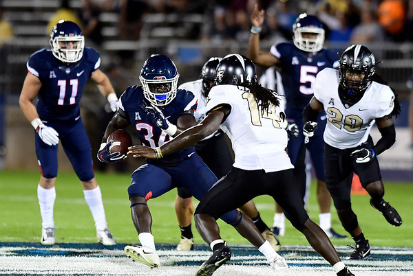 8/30/2018 Mike Orazzi | Staff UConn's Kevin Mensah (34) and UCF's Nevelle Clarke (14) at Rentschler Field in East Hartford Thursday night.