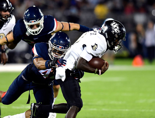 8/30/2018 Mike Orazzi | Staff UConn's Ian Swenson (44) and UCF's Adrian Killins Jr. (9) at Rentschler Field in East Hartford Thursday night.