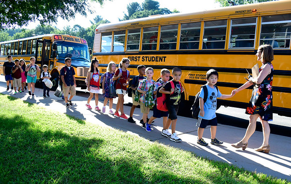 8/30/2018 Mike Orazzi | Staff Marci Silverhart leads children off the bus on the first day at the Mt. View School on Thursday morning in Bristol.