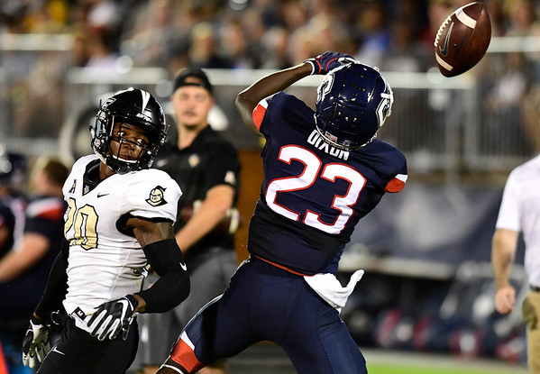 8/30/2018 Mike Orazzi | Staff UConn's Keyion Dixon (23) and UCF's Brandon Moore (20) at Rentschler Field in East Hartford Thursday night.
