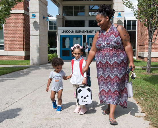 08/30/18 Wesley Bunnell | Staff Lincoln Elementary School Kindergartner Avaleice Bobe, age 5, holds hands with brother Avery Bobe, age 1, and mother Tashana Bryant after her first day of school on Thursday .
