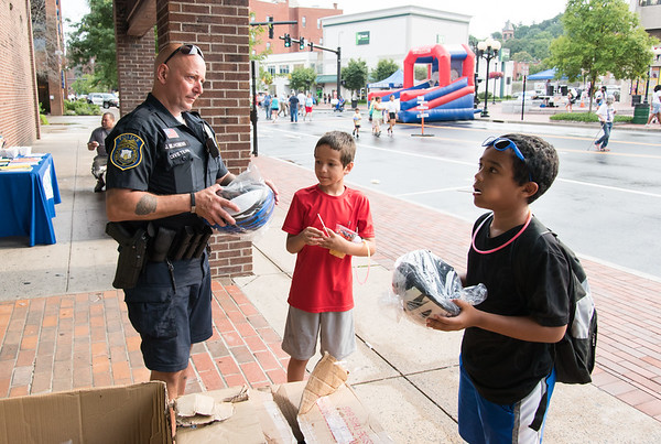 08/07/18 Wesley Bunnell | Staff New Britain Police held their annual National Night Out 2018 on Tuesday evening in a blocked off Central Park area. Officer Joe Milhomens helps Cesar Borrero, age 8 middle, and Juelz Vega, age 11, pick out the right size bicycle helmets.
