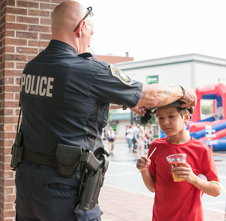 08/07/18 Wesley Bunnell | Staff New Britain Police held their annual National Night Out 2018 on Tuesday evening in a blocked off Central Park area. Officer Joe Milhomens helps Cesar Borrero, age 8, try on a bicycle helmet for the proper fit.