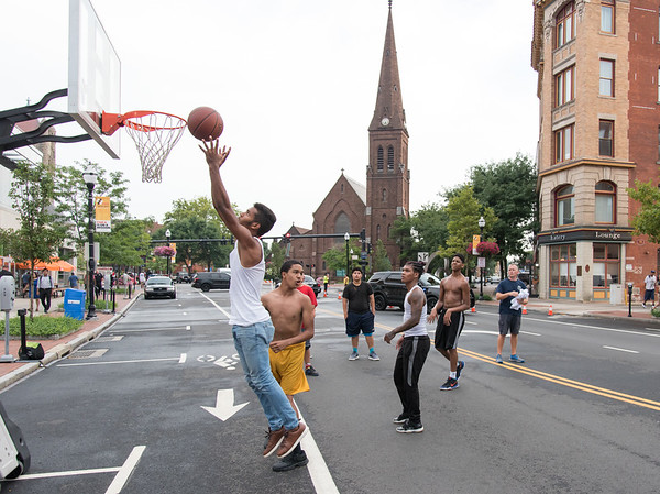 08/07/18 Wesley Bunnell | Staff New Britain Police held their annual National Night Out 2018 on Tuesday evening in a blocked off Central Park area. Lester Olivares with a defensive rebound during a basketball game run by SRO Jerzy Chmura, far right.