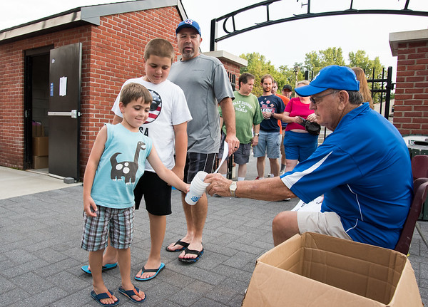 08/08/18 Wesley Bunnell | Staff Bristol Blues volunteer Spencer Hardy, R, hands out souvenir cups to Coltyn Surreira, age 5, and his brother Bradyn, age 10, and dad John on Wednesday night before their semi final game vs the Worcester Bravehearts.