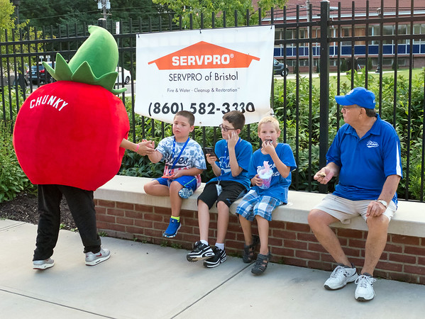 08/08/18 Wesley Bunnell | Staff Sam Mahaney, age 8, shakes hands with Bristol Blues mascot Chunky the Tomato as he sits with friends Tyler Veilleus, age 11, Lucas Clukey, age 8, and Blues volunteer Spencer Hardy at Muzzy Field on Wednesday night. The Blues took on the Worcester Bravehearts in a FCBL semi final playoff game.