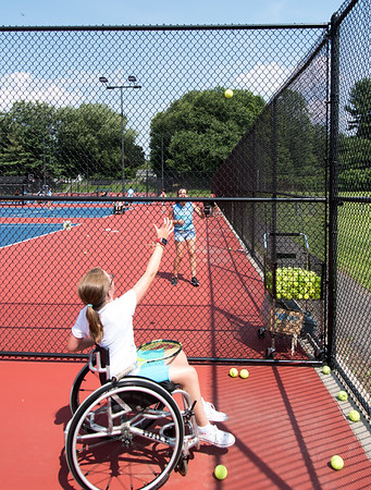 08/08/18 Wesley Bunnell | Staff Lauren Sargent from Hamilton Mass makes a game of tossing tennis balls to a volunteer over the fence at Berlin High School on Wednesday afternoon during The Hospital for Special Care's Ivan Lendl Adaptive Sports Camp. The camp is held every summer for youth with physical disabilities ages 6-19.