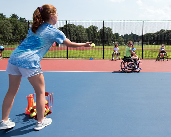 08/08/18 Wesley Bunnell | Staff Volunteer Cecily Meehan from Farmington tosses tennis balls to Catherine Faherty, from Norwell Mass, as she works on her backhand during The Hospital for Special Care's Ivan Lendl Adaptive Sports Camp this week at Berlin High School. The camp is held every summer for youth with physical disabilities ages 6-19.