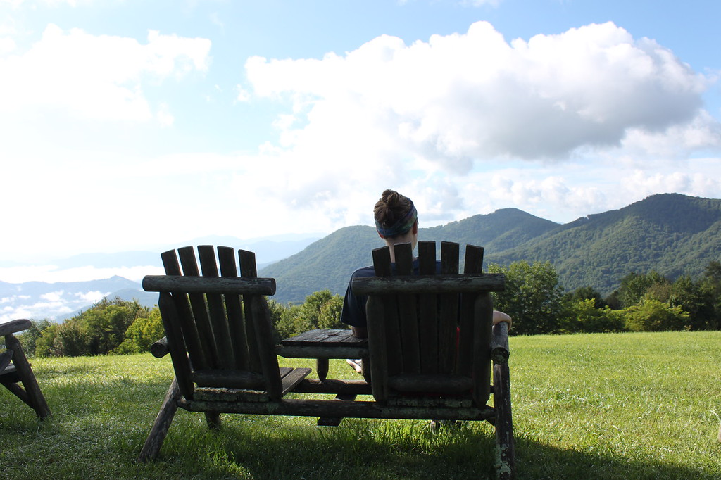 A girl sits in an Adirondack chair overlooking the mountains at The Swag Waynesville