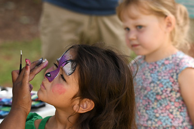The next child in line kept a close watch on the face painting process.