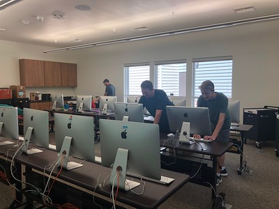Several students enrolled in the IT program at CORE Butte Charter School, including Jacob Kincheloe, right, are paid interns working on the new Mac computer lab in the new high school building on Tuesday, August 6, 2019. (Natalie Hanson --Enterprise-Record)