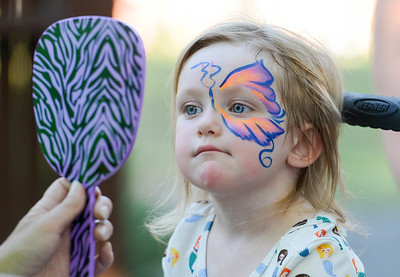 Hazel Patterson, 2, checks out her newly painted face during National Night Out at Capre Acres on Tuesday in Chico. (Matt Bates -- Enterprise-Record)