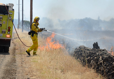 A firefighter sprays water Tuesday on a vegetation fire near Bruce Road in Chico. (Matt Bates -- Enterprise-Record)