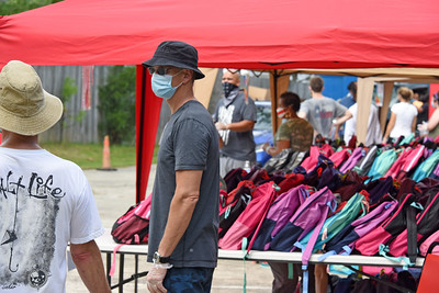 Masked and gloved volunteers were stationed at the individual tents with backpacks filled for students in specific age groups. (Bill Giduz photo)
