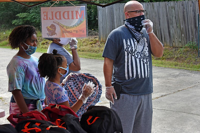 Dozens of masked volunteers worked for hours to hand out more than 600 backpacks to local students in need. COVID-19 turned the annual event into a drive-through, but it still worked. (Bill Giduz photo)