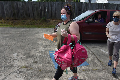 Masked volunteer Lindsey Ammons and others retrieved backpacks from the tents and delivered them to vehnicles, and the awaiting arms of students or parents. (Bill Giduz photo)