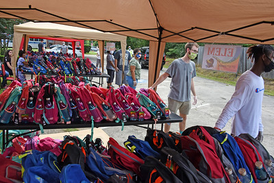 Volunteers from local churches stood by tables filled with more than 600 brightly colored backpacks. (Bill Giduz photo)