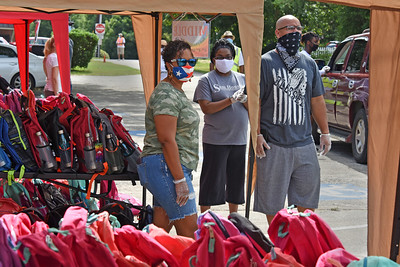As families drove through, volunteers selected backpacks from tents labeled Elementary, Middle, and High. (Bill Giduz photo)