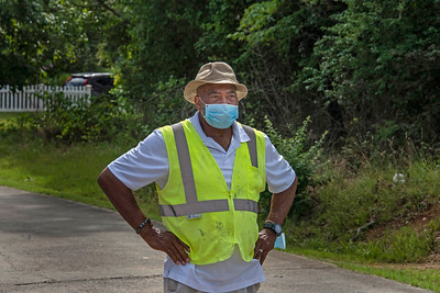Marvin Brandon was among more than a dozen volunteers who held the distribution event run with surgical precision. Recipients arrived in cars and lined up around the church. Masked volunteers met them on the other side and handed them their backpacks through the car window. (Bill Giduz photo)