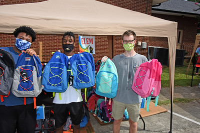 These volunteers showed off some of the small backpacks of school supplies intended for elementary school students. (Bill Giduz photo)