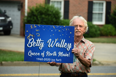 Neighbor Larry Ligo holds up the sign that was created to celebrate long-time resident Betty Walley. (Bill Giduz photo)