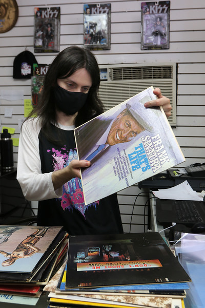 Zack Frediani looks up a Sinatra album at The Vinyl Vault in Littleton, which sells records including LPs and 45s, as well as cassettes and DVDs. His father Greg Frediani owns the store.  SUN/Julia Malakie