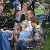 Dad Hugh Rosen helps baby Harvey Rosen dance while Hugh's son Peter, middle, and James Jenkins, right, watch the concert. The group attended Thursday evening's FACE Orchestra concert in downtown Effingham.