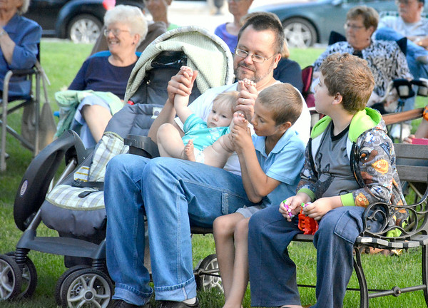 Dad Hugh Rosen helps baby Harvey Rosen dance while Hugh's son Peter, middle, holds a foot and James Jenkins, right, looks on. The group attended Thursday evening's FACE Orchestra concert in downtown Effingham.