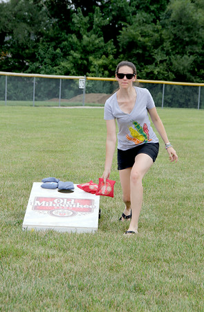 Kelly Pickering throws a bean bag during a bag tournament at the St. Anthony Parish Picnic Sunday afternoon.<br /> Tony Huffman photo